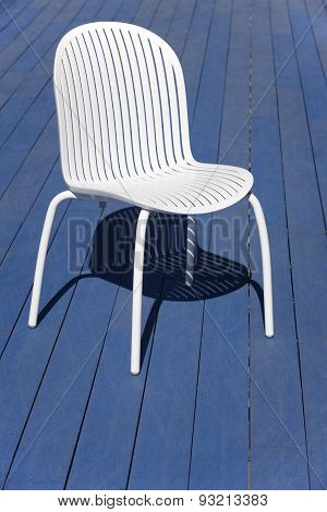 White Plastic Chair Over A Blue Wooden Floor. Outdoor