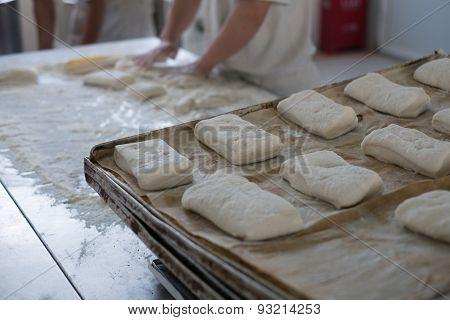 Baker And Tray Of Fresh Ciabatta Bread Buns