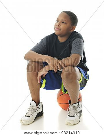 A preteen boy sitting on his basketball while looking for other players to show up.  On a white background.
