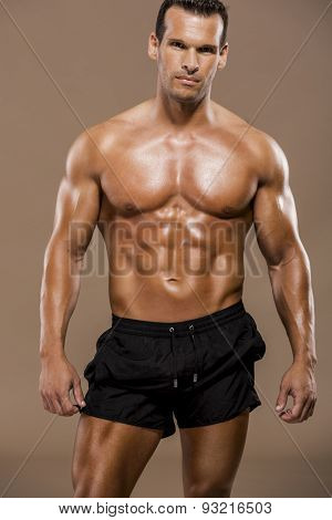 Muscle man posing in studio over a brown background