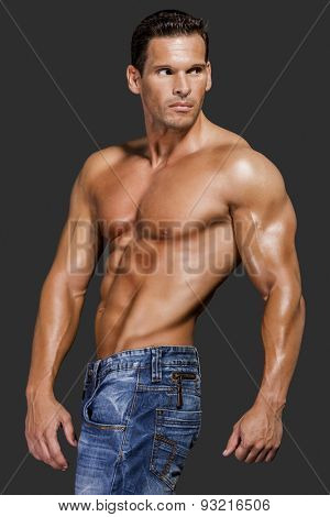Muscle man posing in studio, isolated over a gray background