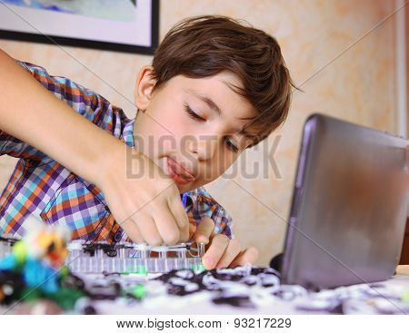 Preteen Handsome Boy Make Rainbow Loom Toy With Online Lesson On Tablet Computer