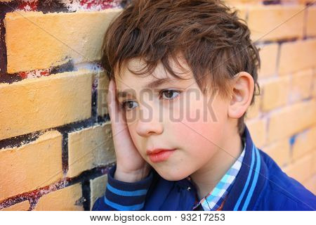 Preteen Handsome Boy Close Up Outdoor Portrait On The Yellow Brick Wall Background