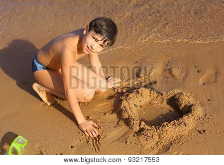 Preteen Handsome Boy Sculpturing Sand Heart On The Red Sea Beach