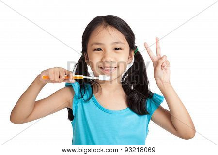 Little Asian Girl Show Victory Sign With Toothbrush