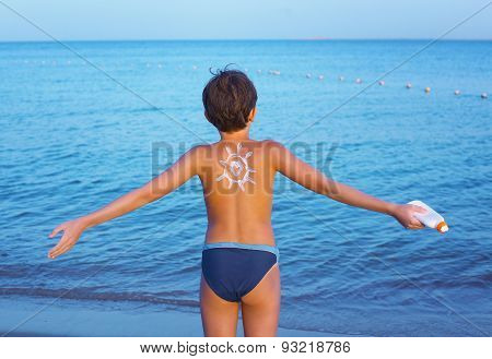 Handsome Preteen Boy With Anti Sunburn Cream Sun Drawing On His Back On The Sea Sand Beach Backgroun