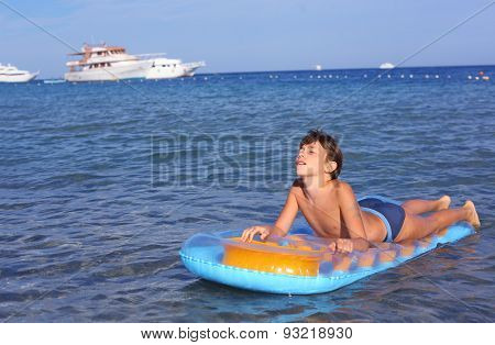Handsome Boy In Swimming Suit With Inflatable Matress On The Blue Sea With Yacht Background