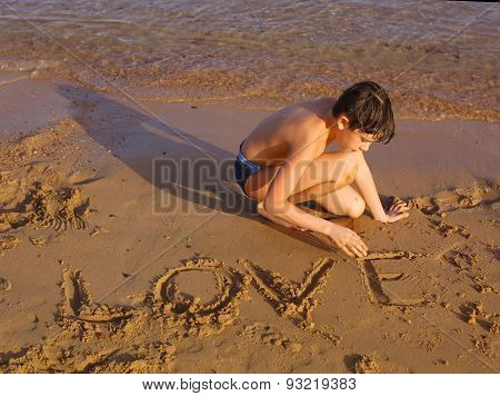 Preteen Handsome Sun Tanned Boy On The Red Sea Beach Whrite Love On The Sand