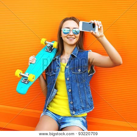 Fashion And Technology Concept - Stylish Young Girl In Colorful Clothes With Skateboard Makes Self-p