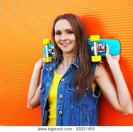 Fashion Portrait Of Hipster Pretty Girl In Colorful Clothes With Skateboard Having Fun Against The O
