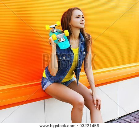 Fashion Portrait Of Pretty Girl In Colorful Clothes With Skateboard Against The Orange Wall