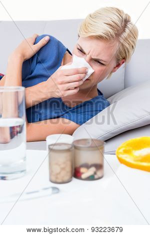 Sick blonde woman blowing her nose and looking at pills on white background