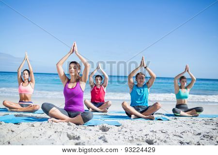 Friends doing yoga together at the beach