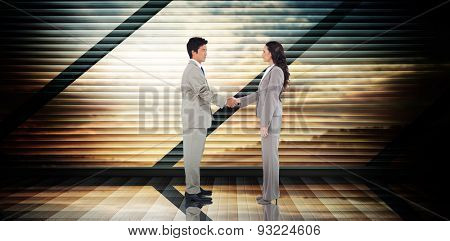 Business people shaking hands against room with large window looking on landscape