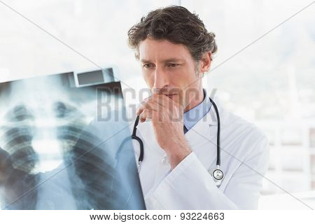 Serious doctor looking at X-ray in medical office