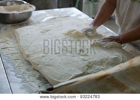 Baker Placing Raw Ciabatta Bread On Tray