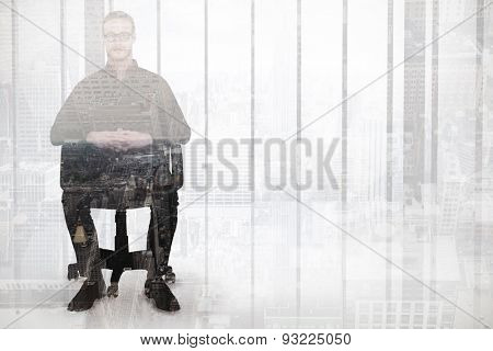 Stern businessman sitting on an office chair against new york