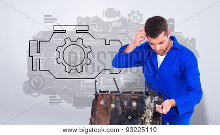 Confused mechanic repairing car engine against grey vignette