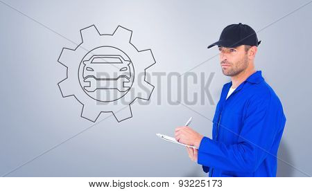 Mechanic in blue overalls writing on clipboard against grey vignette