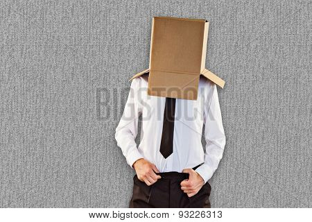 Anonymous businessman with hands in waistband against grey background