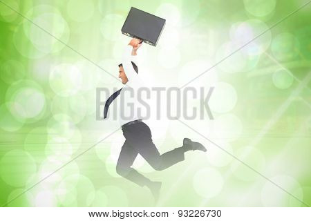 Smiling businessman leaping while briefcase against green abstract light spot design