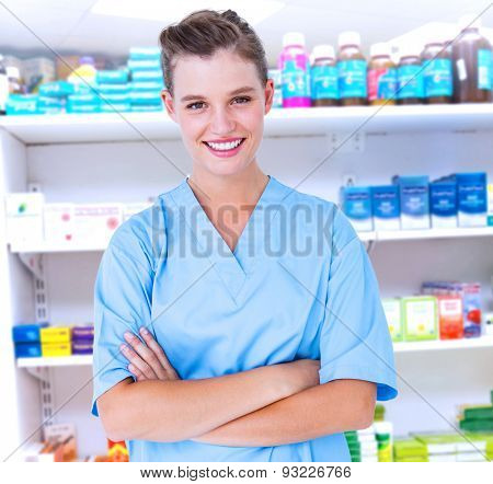 Smiling nurse in blue scrubs posing with arms crossed against close up of shelves of drugs Smiling nurse in blue scrubs posing with arms crossed on white background