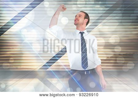 Businessman cheering with clenched fist against window overlooking city