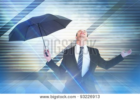 Businessman sheltering under black umbrella testing against window overlooking city