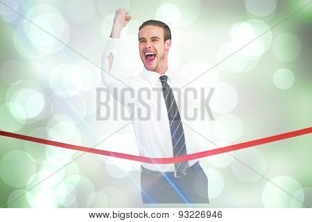 Businessman crossing the finish line while clenching fist against grey abstract light spot design