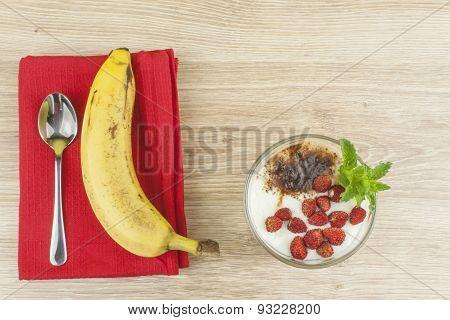 Homemade yogurt, oatmeal with strawberries, banana and chocolate. Sprinkled with cocoa.