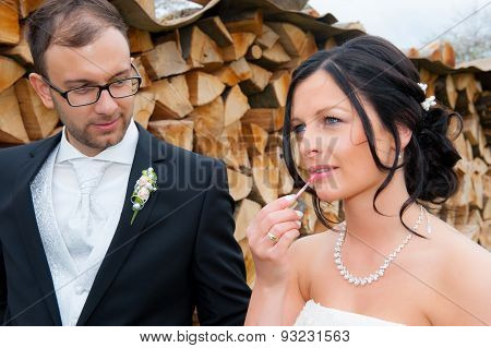 Young Bridal Couple  In Front Of Wooden Background