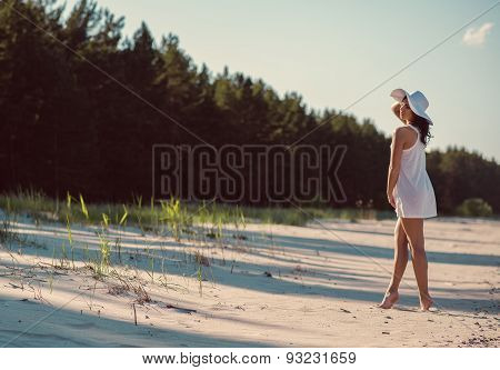 Woman Wearing White Short Dress And White Hat Posing On The Beach