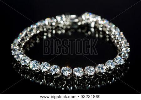 golden bracelet with precious stones on black background