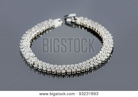 golden bracelet with precious stones on grey background