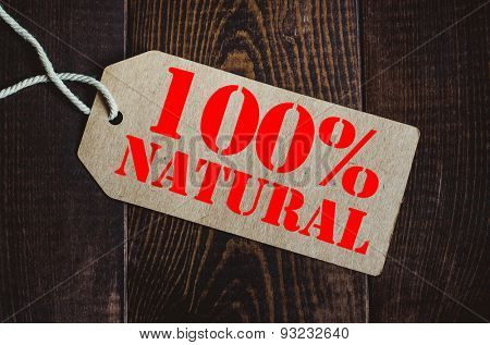 100 % natural. Blank tag on dark wood background