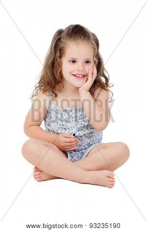 Pensive little girl with three year old sitting on the floor isolated on a white background