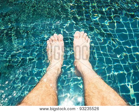 Male legs relaxing in the swimming pool.