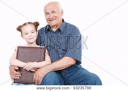 Grandfather reading a book with granddaughter