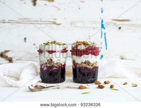 Yogurt oat granola with berries, honey and nuts in glass jars, rustic white  background