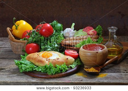 Open Pie With Egg And Cutlets On A Skewer Submitted With Sauce And Fresh Vegetables