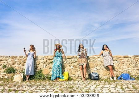Young Women Girlfriends Using Smartphone Outdoors With Mutual Disinterest Towards Each Other