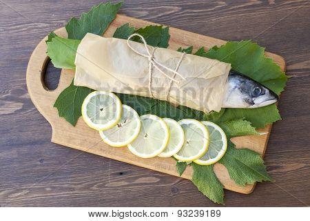 Fresh mackerel on paper in grape leaves with lemon