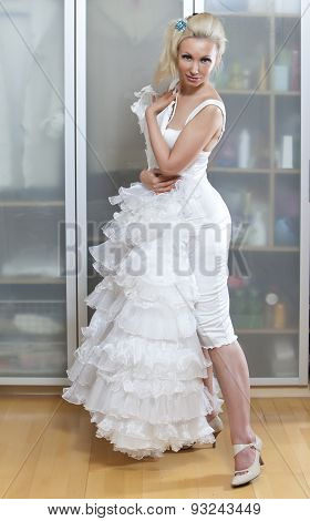 The young woman near wedding dress dreams about wedding