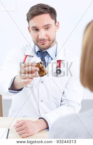 Smiling cardiologist giving pills to the patient