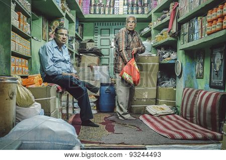 JODHPUR, INDIA - 07 FEBRUARY 2015: Shop owner waiting while customer looks for goods to buy. Shop owners also stay in stores until late working hours.Post-processed with added grain and texture.