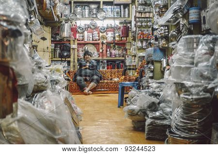 JODHPUR, INDIA - 07 FEBRUARY 2015: Shop owner with hat sitting on couch and resting before closing time. Post-processed with added grain and texture.