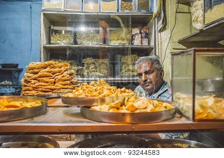 JODHPUR, INDIA - 16 FEBRUARY 2015: Vendor sits in store with various food on metal plates and noodles on shelves. Post-processed with grain and texture.