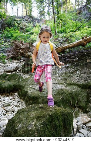 Fearless Little Girl Scout Jumping Over Stones