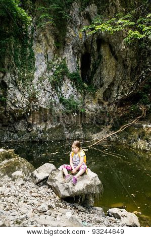 Pensive Little Girl Sitting On A Big Rock By A Small Pond