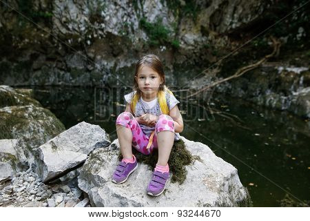 Happy Little Girl Resting On A Big Rock By A Small Pond